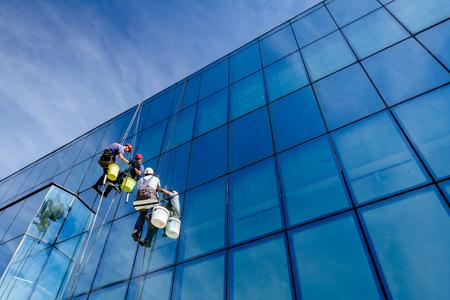 Los escaladores industriales están aplicando silicona a la unión de caucho entre la fachada de vidrio del edificio. Foto de archivo