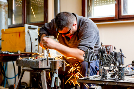 Sculptor is using arc welding to assembly metal sculpture barehanded with protective spectacles. Stok Fotoğraf