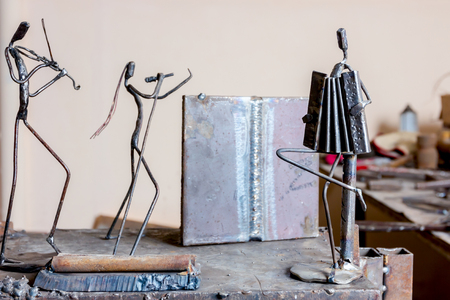 Figures of music performers are made with welded metal wire. Accordion, violin and vocal are performing together. Living lines