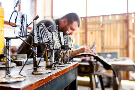 Sculptor is making creative figures of musicians of metal wire in his workshop. Accordionists are playing together. Stok Fotoğraf