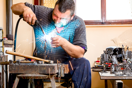 Sculptor is using arc welding to assembly metal sculpture without proper protection, barehanded.