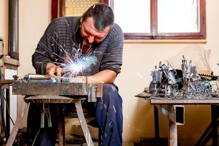 Lo scultore utilizza la saldatura ad arco per assemblare sculture di metallo senza un'adeguata protezione, a mani nude.