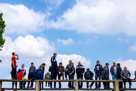 Chestereg, Vojvodina, Serbia - April 30, 2017: Group of people, mostly men is gathered on public happening. Fans are standing on grandstand for better view.