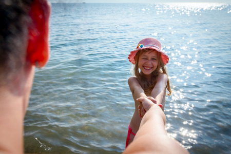 Asking to follow me. Happy child girl with summer hat is holding hands and invite their parent to go with her in sea water. Banque d'images - 107805447