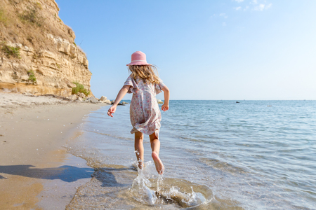 Young woman, child in hat and cute summer dress is running and splashing in shallow water, the sea shore.