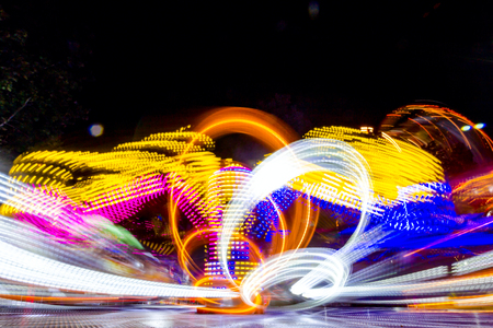 Long exposure of a fast spinning colorful carousel illuminated at night with vivid lightings