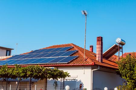 I pannelli a celle solari utilizzano l'energia solare rinnovabile per produrre elettricità, posizionati sul tetto della casa. Moderna tecnologia per il risparmio energetico