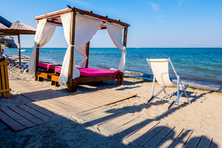 Luxury comfortable wooden pergola with white curtain for sunshades is placed on the sunny beach. Standard-Bild