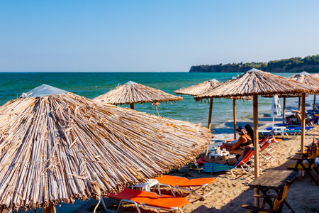 Above view on sunshades, umbrellas and deckchairs with people, tourists at public beach for a perfect holiday.