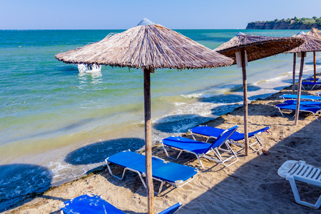 Above view on sunshades, umbrellas and plastic deckchairs are placed at public beach for a perfect holiday.