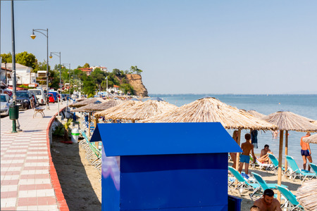 Blue metal wear changing cabin on the sandy beach with thatched sunshades, umbrellas and deckchairs, tourists are next to the coastline.