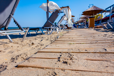 Wooden path is going, through sandy empty public beach, umbrellas and deckchairs for a perfect holiday. 版權商用圖片