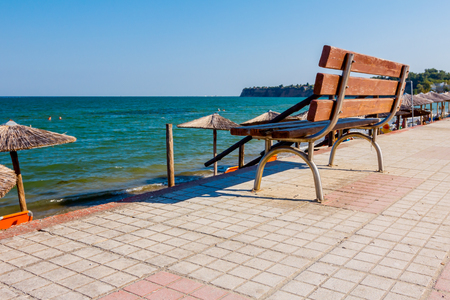 Wooden bench is placed on tiled walkway behind, but above public beach with deckchairs next to the coastline. 版權商用圖片