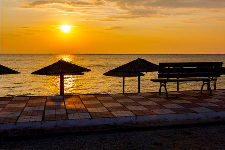 View at early morning Sun, dawn, on public beach with thatched sunshades. Wooden bench is placed on tiled walkway. 版權商用圖片