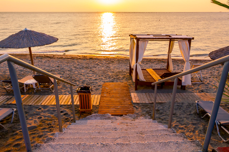 Stairs are going down to the beach with umbrellas and loungers placed next to the coastline, along water edge at early morning Sun, dawn.
