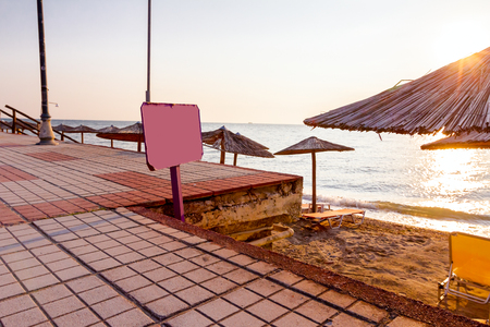 Information banner, colored wooden board is standing in front of public beach, morning time, dawn. 版權商用圖片