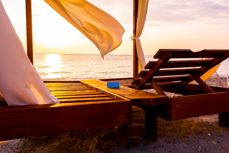 View at early morning Sun, dawn, on public beach with reservation metal plate on luxury and comfortable wooden pergola.