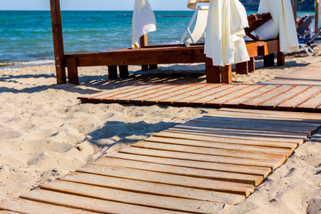 Wooden path is going, through sandy beach, to the comfortable wooden pergola with white curtain sunny beach. Standard-Bild