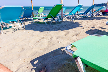 View on empty public beach with thatched sunshades, umbrellas and plastic deckchairs for a perfect holiday.
