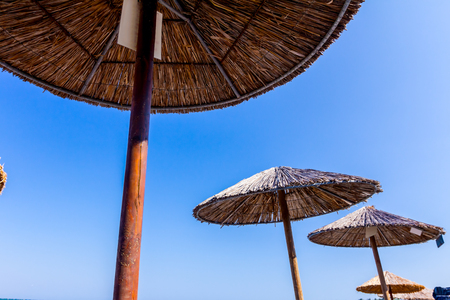 Thatched beach umbrella shot from underneath over blue sky. Made with wood and reed