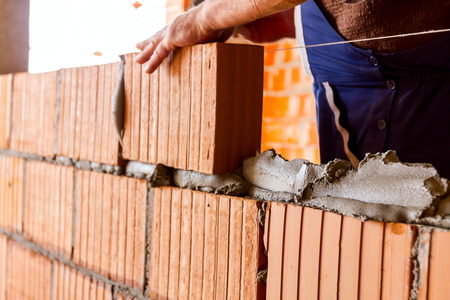 Mason, bricklayer worker is using red blocks to mount a wall next the string line to be straight. Archivio Fotografico