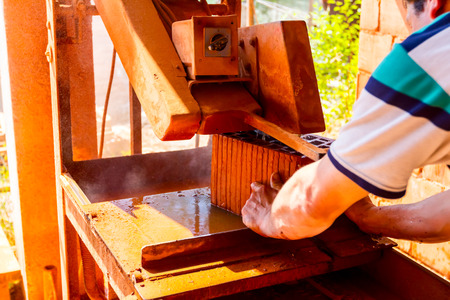 Worker is using power tool to makes clean precise cut in red brick, block. It uses abrasive action to slice through material as the saw rotates at high speed.