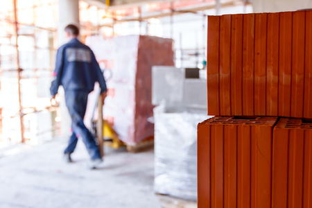 Pile of red blocks, in background worker is using manually forklift for delivery pallet packed in plastic foil. Stock Photo