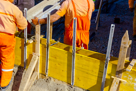 Workers at building site are pouring concrete in long mold from mixer truck. Stock Photo