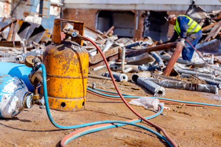 Oxygen and butane gas are in cylinder tanks with attached gauge regulators, manometers. Worker is cutting scrap metal with torch at junkyard.
