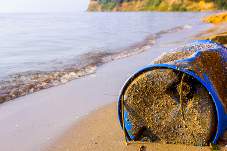 Used blue plastic drums for storing water and other liquids is washed up by the sea on sandy beach, waste.