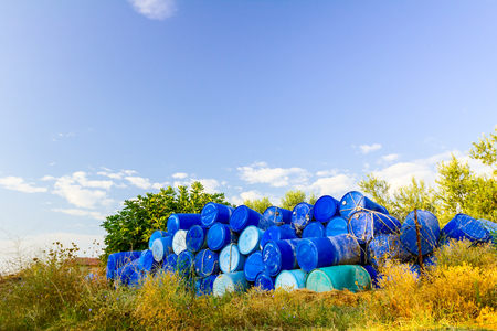Stockpile of used blue plastic drums for storing water and other liquids.