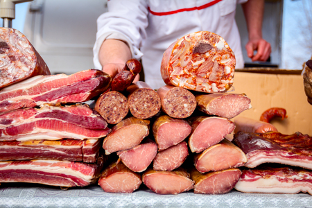 Various smoked meat for sale placed outdoor at flea market.