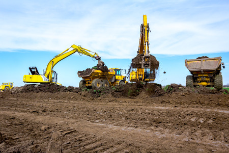Big excavators are filling two dumper trucks with soil at construction site, project in progress.