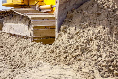 Close up view on bulldozers undercarriage during pushing sand at construction site. Stok Fotoğraf