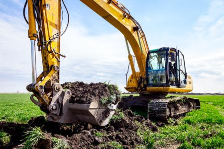 Big excavator is excavating soil at construction site, project in progress. Reklamní fotografie