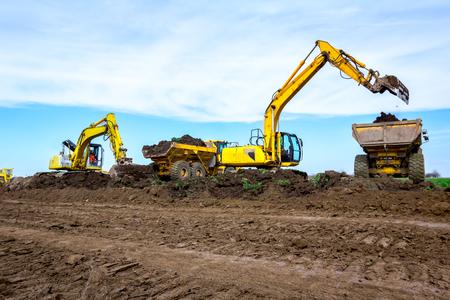 Große Bagger befüllen auf der Baustelle zwei Muldenkipper mit Erde, Projekt läuft.