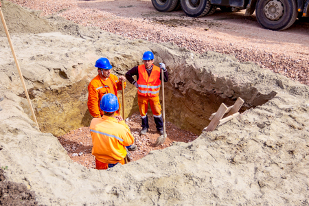 Zrenjanin, Vojvodina, Serbia - March 30, 2018: Construction workers are using shovels to realign level of gravel in square base trench.