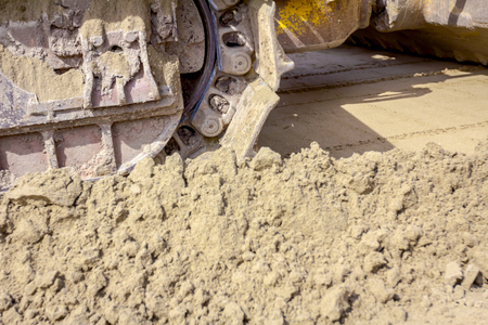 Close up view on bulldozer's undercarriage during pushing sand at construction site. Stok Fotoğraf
