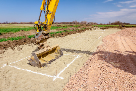 Excavator will excavate square trench that is marked with white powder lime at construction site, project in progress. Stockfoto