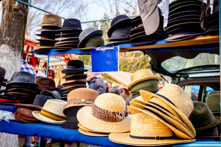 Stacked straw and cloth hats are for sale, available at flea market.