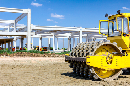 Huge road roller with spikes is compacting soil, sand at building site.