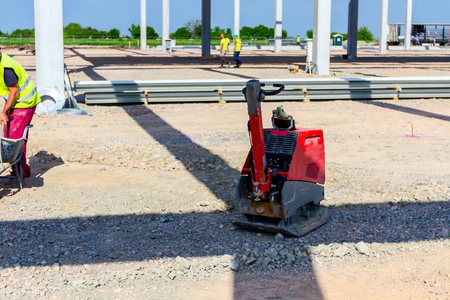 Used plate compactor, vibratory hammer, jumping jack machine, power tool placed in shadow at construction site. Stockfoto