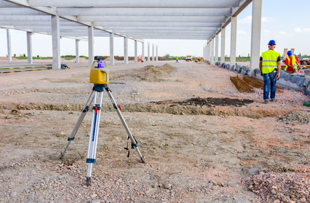 Total center device on tripod with laser for leveling other devices to level construction site. 版權商用圖片