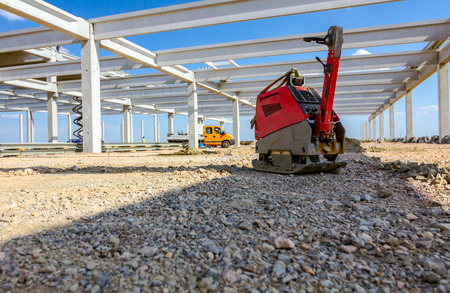 Used plate compactor, vibratory hammer, jumping jack machine, power tool placed in shadow at construction site. Reklamní fotografie