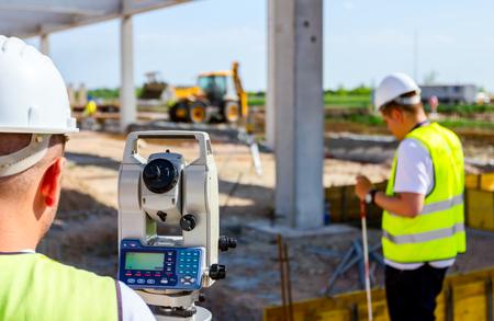 El ingeniero topógrafo está midiendo el nivel en el sitio de construcción. Los topógrafos aseguran mediciones precisas antes de emprender grandes proyectos de construcción.