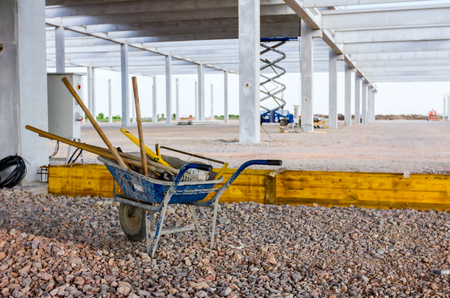 View on wheelbarrow with used equipment for earthworks at construction site. Stock Photo - 120898110