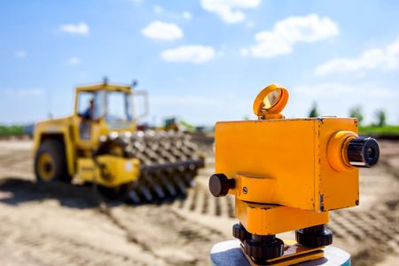 Vermessungsinstrument zum Messen des Niveaus auf der Baustelle, Walze mit Spikes verdichtet den Boden auf der Baustelle im Hintergrund.