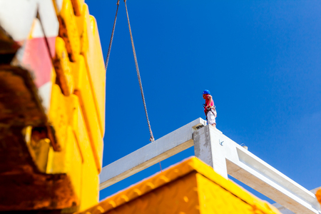 Worker is helping mobile crane to manage concrete joist for assembly huge construction. Stock Photo