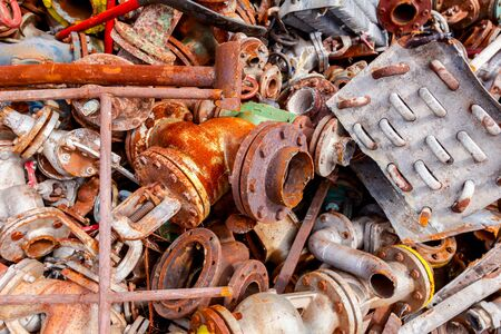 Pile of scrap metal, old cooling system and industrial parts, pipes and valves after cassation.