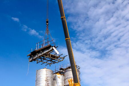 Crane is bringing down part of heavy metal construction in industrial complex.
